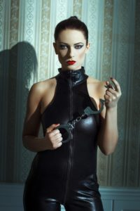 Image of woman in leather holding handcuffs