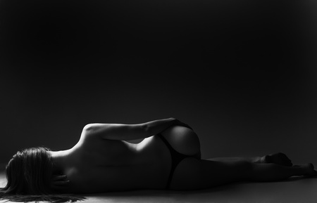 Low Light photo of woman lying naked on side