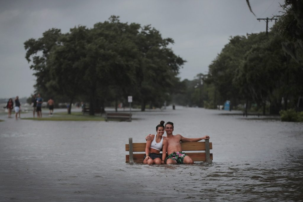 MANDEVILLE, LOUISIANA - JULY 13: People sit on a park bench along Lakeshore Drive on the shore of Lake Pontchartrain after the area flooded in the wake of Hurricane Barry on July 13, 2019 in Mandeville, Louisiana. The storm, which made landfall this morning as a category one hurricane near Morgan City, caused far less damage and flooding than had been predicted. Flash flood watches were issued throughout much of Louisiana and as far east as the Florida panhandle as the storm was expected to dump more than a foot of rain in many areas and up to 25 inches in some isolated locations. Many areas are now expected to get less than half of the original projections.   Scott Olson/Getty Images/AFP == FOR NEWSPAPERS, INTERNET, TELCOS & TELEVISION USE ONLY ==