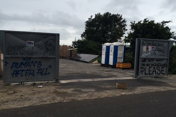 Graffiti along a metal fence on the outskirts of the Calais Jungle
