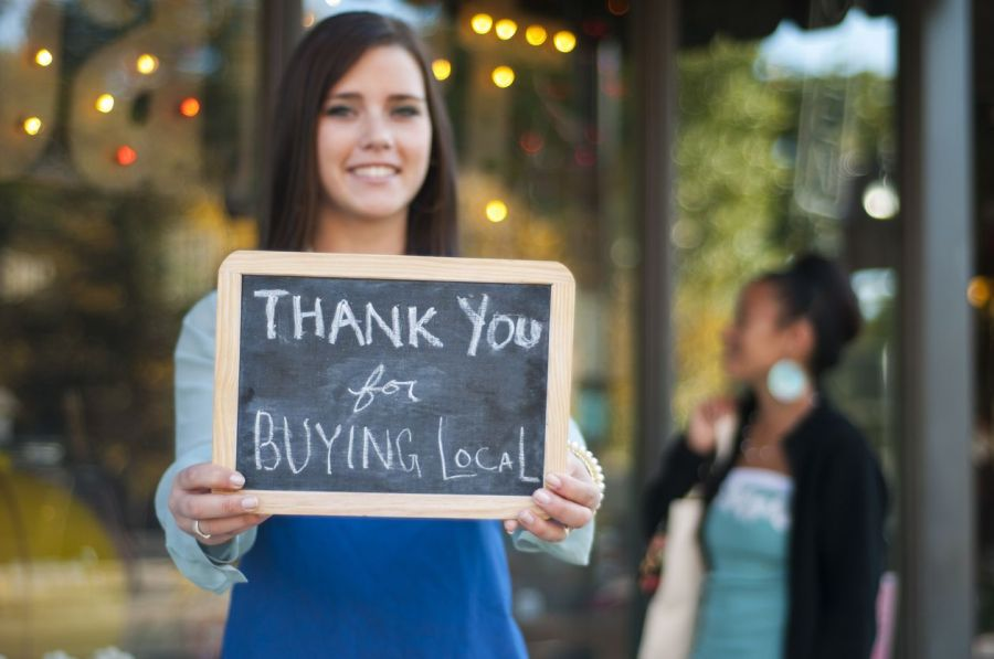 PointofSale Business owner holding thank you for buying local sign Small town businesses