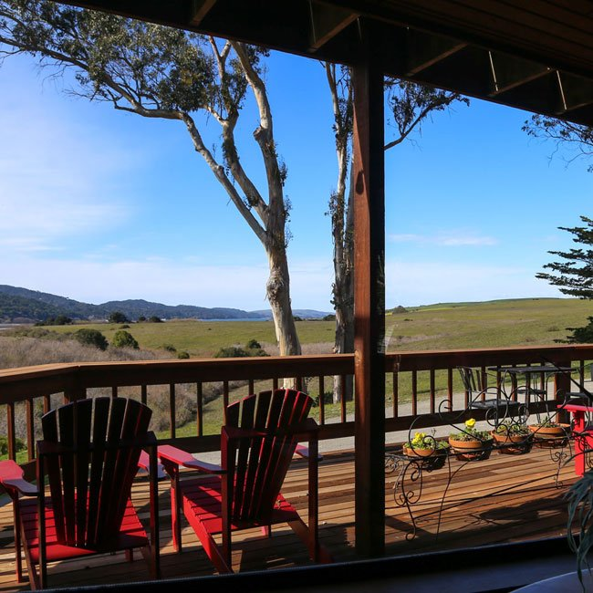 View of the deck and hills and trees and mountains.