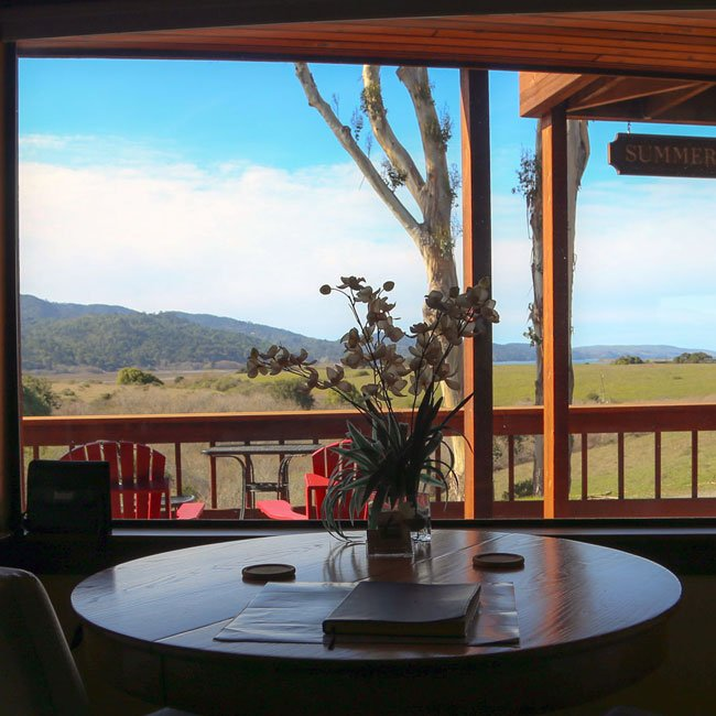 View of the deck and mountains and hills from inside the Ridge View Room.