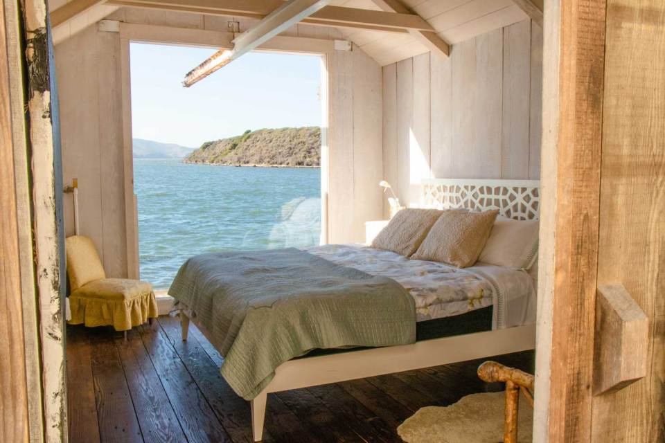 View of Tomales bay from love shack bedroom, with bed and chair.