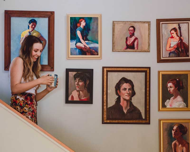 Woman walking down stairs with paintings on the back wall.