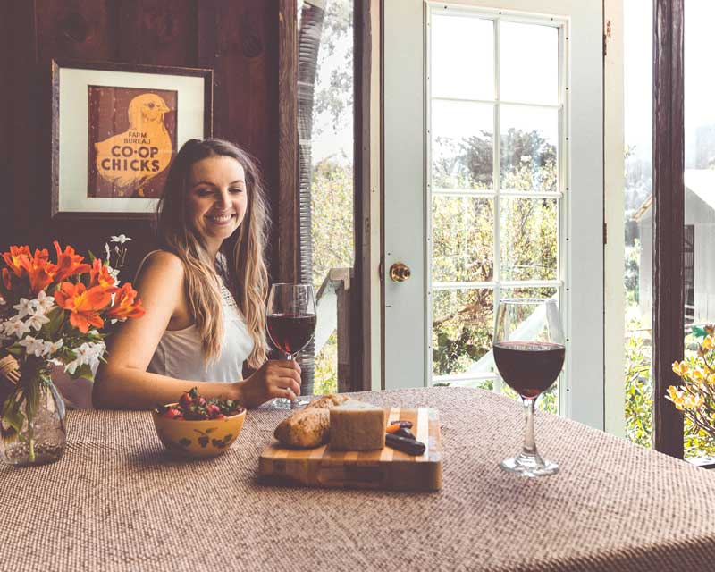 Woman sitting at a table with wine and snacks.