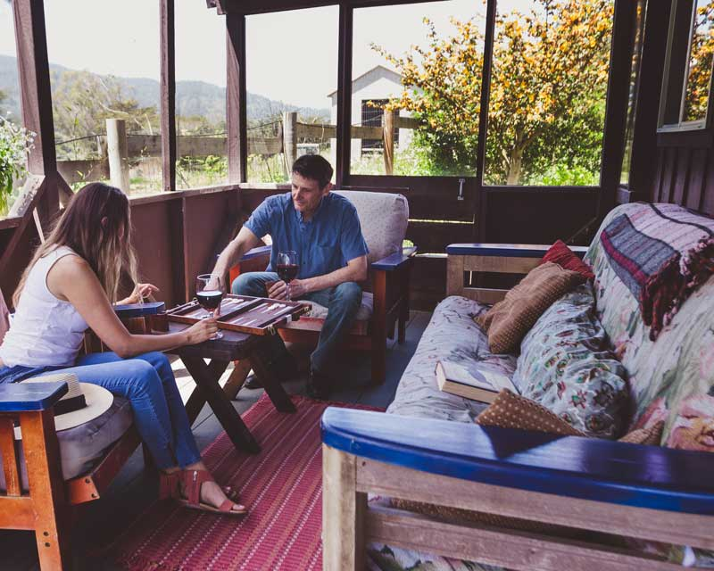 Man and woman playing a board game in an enclosed patio.