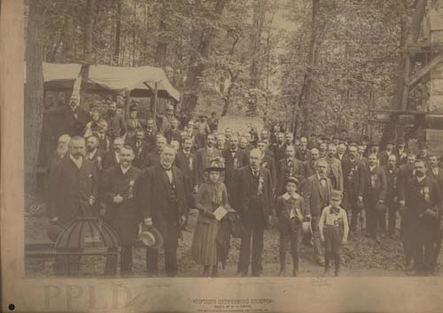 Vintage speia toned photo of a gathering of people outsdoors posing an looking at camera