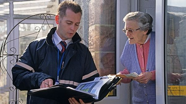 door to door salesman talking to elderly woman