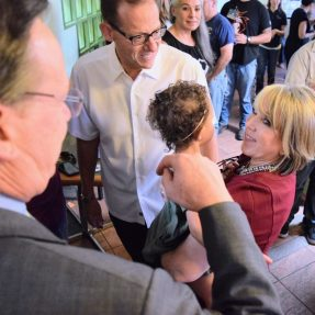Michelle Lujan Grisham holds her granddaughter while flanked by State Treasurer Tim Eichenberg and Democratic candidate for State Auditor, Brian Colon (right).