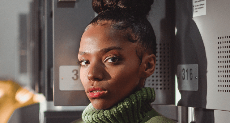 Stylish young black woman in a turtleneck wearing a top knot