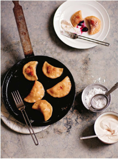 pierogi in a skillet with some on a plate