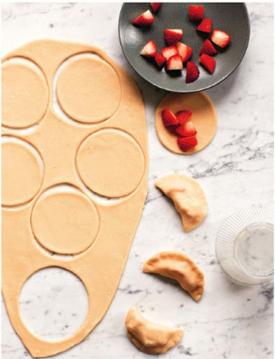 dough rolled out on marble slab, bowl of strawberries, and pierogi in the making
