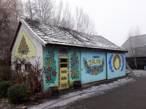 a small building in Zalipie, Poland decorated with floral paintings with a little snow on the wooden shingle roof