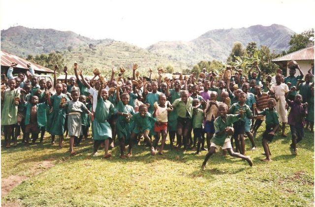 large group of ugandan children laughing and waving madly at the camera