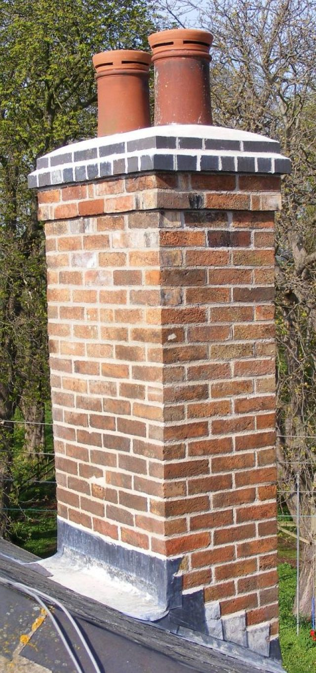 repointed chimney stack with new brickwork to top and blue brick cap