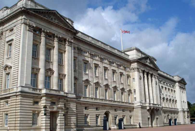 Facts about Buckingham Palace: The front façade of Buckingham Palace with the Union Jack flying high on a sunny day
