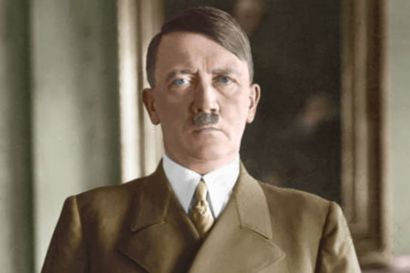 Facts about Adolf Hitler: a colorized photo of his official 1938 portrait, with Hitler stood in front of a painting staring into the camera.
