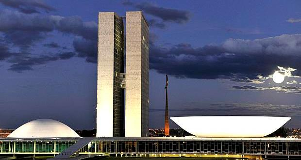 Fchada do Congresso Nacional durante o fim da tarde. São mostradas duas torres prediais, ao fundo aparecem nuvens densas