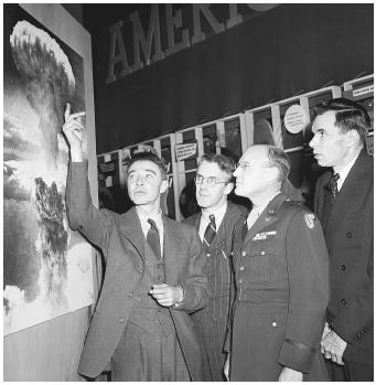 """J. Robert Oppenheimer, Professor. H. D. Smythe, General Nichols, and Glen Seaborg look at a snapshot of the atomic blast on Hiroshima in 1946. Oppenheimer was later stripped of his security clearance due to apparent """"Communist sympathies."""""""