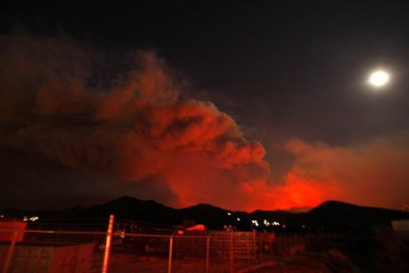 (Genaro Molina / Los Angeles Times / August 30, 2009) Smoke from the Station fire billows as the moon glows over Soledad Canyon Road in Acton.