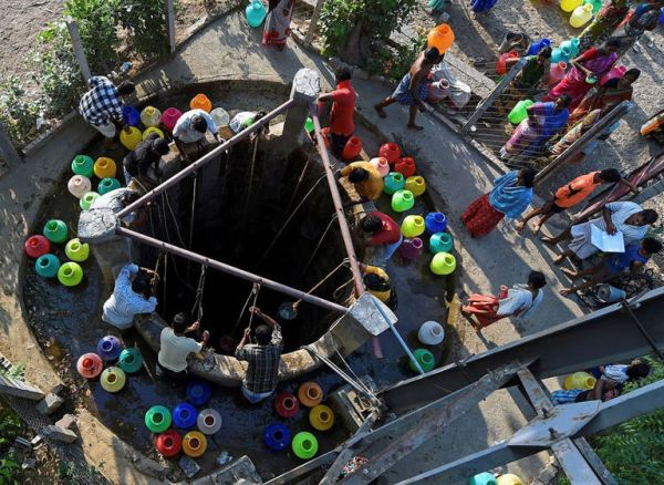 People chosen after a draw of lots collect water from a community well at Eswari Nagar in Chennai. (Image: PTI)