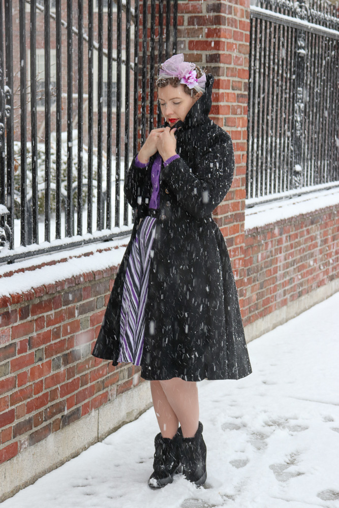 Black 50s princess coat worn over a purple cardigan and striped skirt on a snowy day