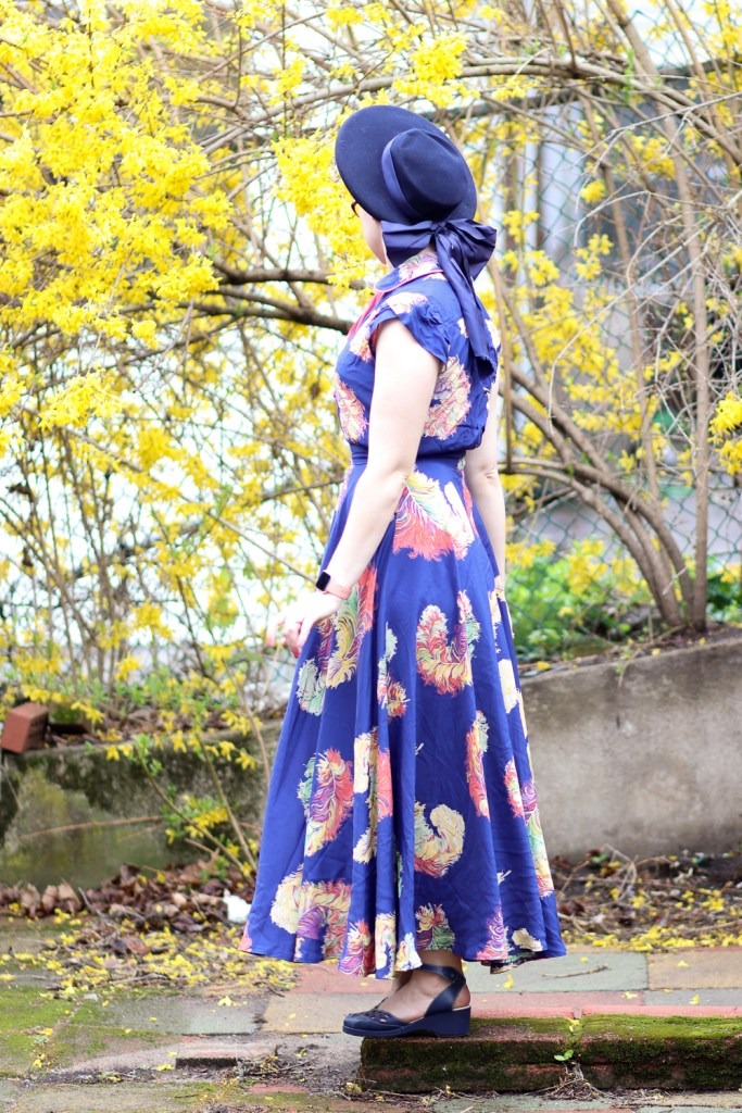 1940s inspired Showgirl Royalty ostrich feather print dress from Trashy Diva in royal blue, yellow, peach, mint, and purple, worn with a large blue hat and blue sandals