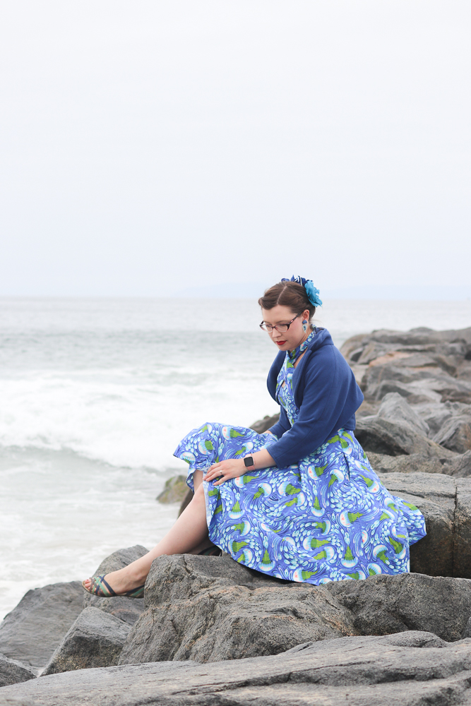 A girl sits on a breakwater wearing a jellyfish-print retro sun dress and a blue fleece bolero