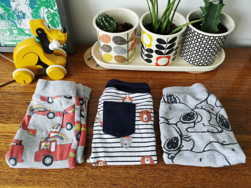 Image displays three pairs of baby joggers purchased as part of a Vinted baby clothes bundle laying on a teak surface with Orla Kiely plants in the background