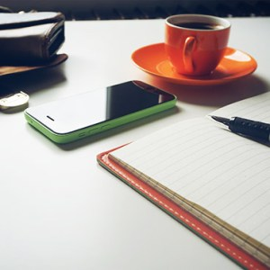 Desktop with phone, coffee cub and notebook