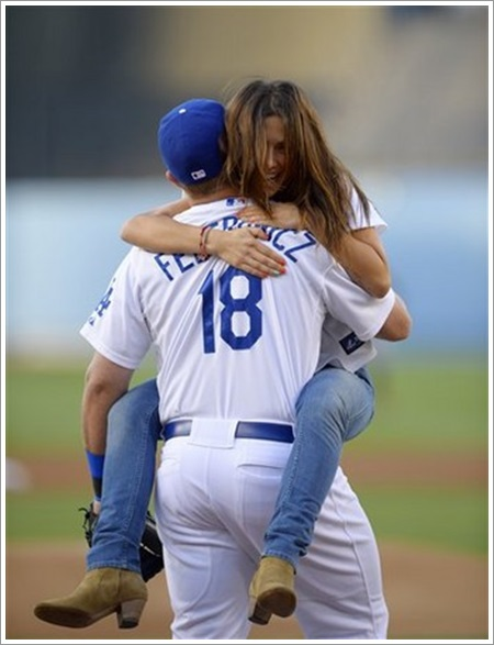 Actress Sarah Shahi jumps into the arms of Los Angeles Dodgers' Tim Federowicz after throwing out the ceremonial first pitch prior to the Dodgers' baseball game against the San Francisco Giants, Monday, June 24, 2013, in Los Angeles. (AP Photo/Mark J. Terrill)