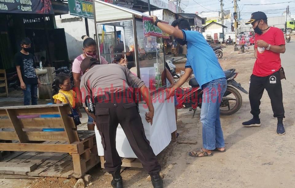 Petugas Polsek bersama Aparatur Kampung bantu pedagang menggeser gerobak jualan takjil