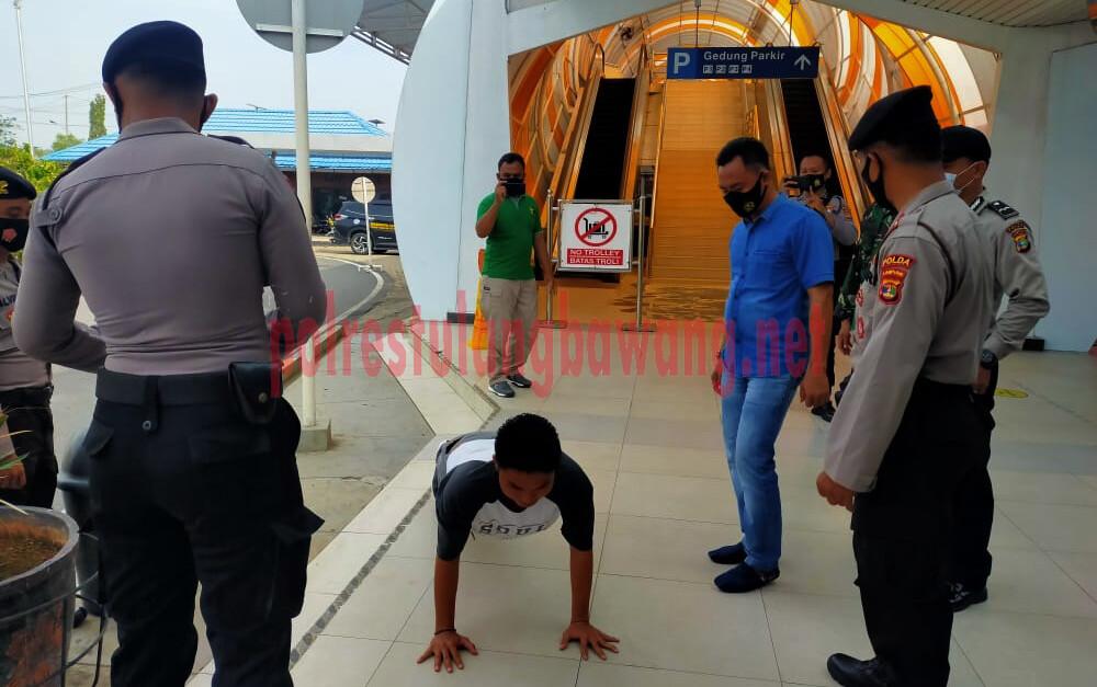 Petugas memberikan sanksi berupa push up kepada warga yang tidak memakai masker di Bandar Udara Internasional Radin Inten II, Natar