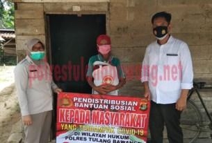 Petugas dari Satresnarkoba Polres Tulang Bawang saat mendistribusikan bantuan sosial kepada warga di Kampung Mekar Jaya, Kecamatan Banjar Baru