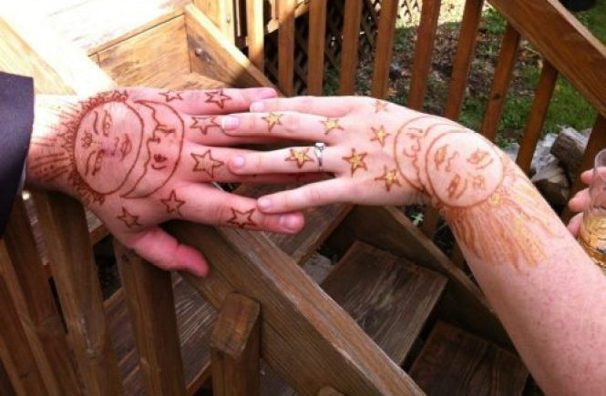 two hands with star henna on them, over a wooden railing