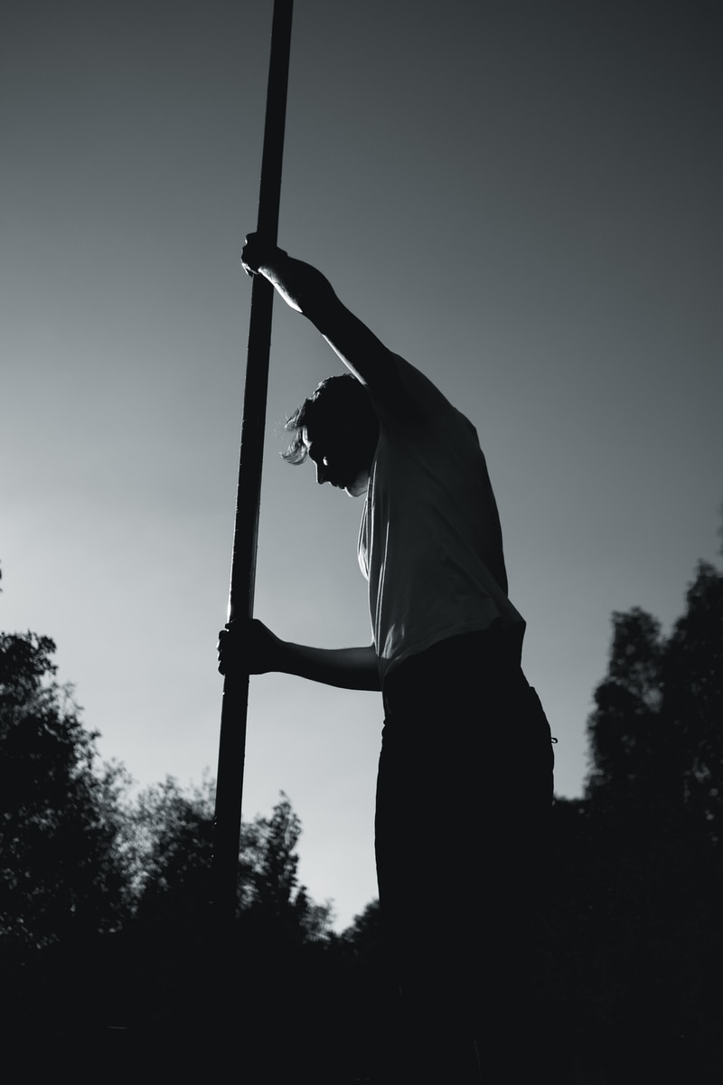man in white shirt holding pole