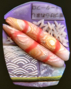"Lindly Haunani, Sushi Brooch, 1993 3"" x 1.25"" x .25' polymer, photo transfer, mokume with aluminum leaf and translucent millefiore"