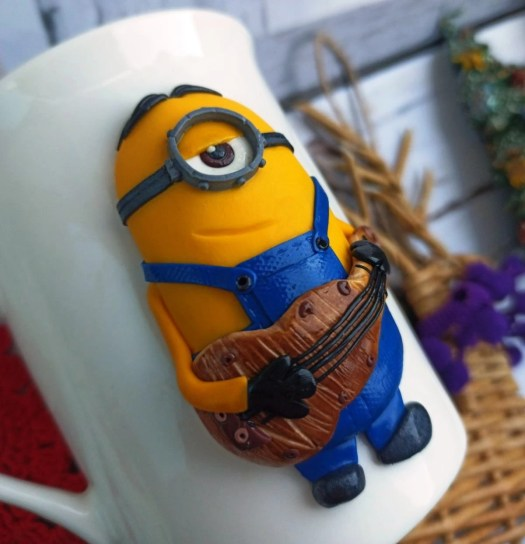 Polymer clay Minion with a guitar on a mug