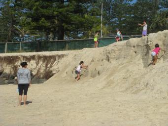 Children are having fun on the escarpment caused by erosion