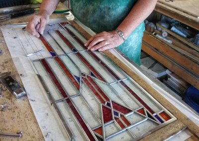 Hands assembling stained glass window