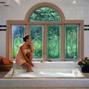 Pompi Glass - Anderson Window - Model sitting edge of bath beautiful 5-light window overlooking garden