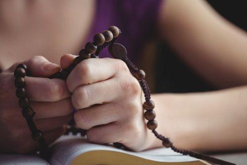 Kobieta modli się na różańcu