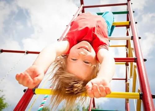 girl hanging upside down on playground