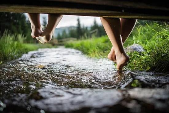 children's feet swinging under dock, above stream