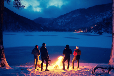 Four people standing around a fire in front of a pond.