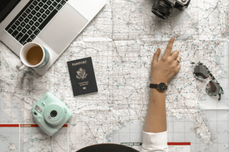 Girl planning a vacation using a map, her computer, coffee, a camera, sunglasses and passport.