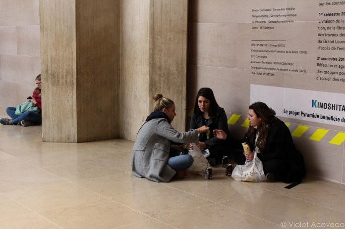 Eating lunch in the lobby of the Louvre. © Violet Acevedo