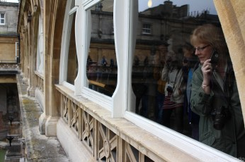 Tourists looking down at the Roman Baths while listening to the audio guide. © Violet Acevedo