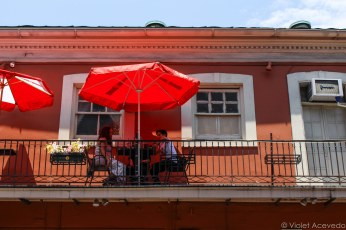 Restaurant goers sit above on the second floor patio in the French Quarter. © Violet Acevedo